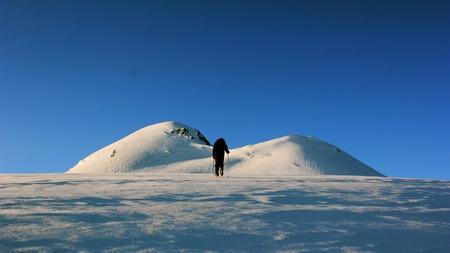 ice axe: man climbs mountain with snowy slopes keeping ice axe