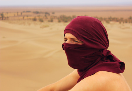 e pretty: man with covered by shawl face in desert looking forward and squinting