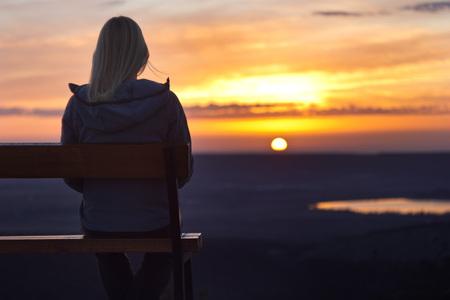 日に見る夕日に花束に座っている女の子