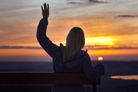 太陽の手に見る夕日に花束に座っている女の子