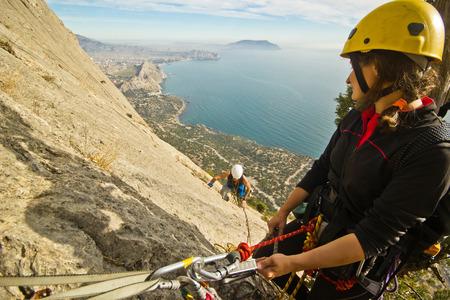 ascend: two rock climbers ascend the mountain near sea Stock Photo
