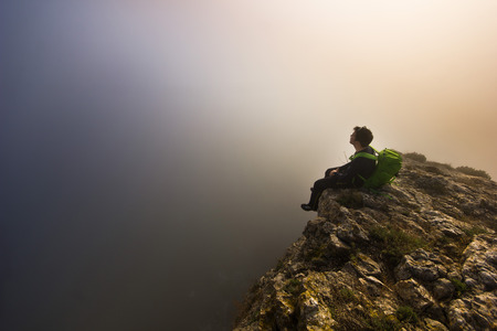 alpinist: man sitting on top of a cliff in foggy weather