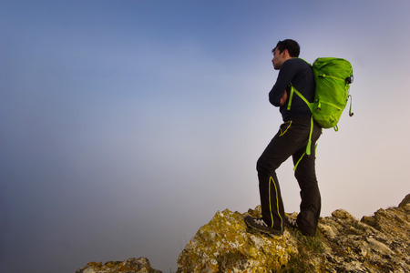 alpinist: man with green backpack standing on a cliff in foggy weather Stock Photo
