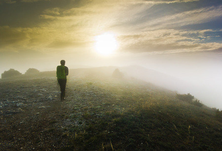 foggy hill: man with backpack walking over a hill in foggy weather Stock Photo