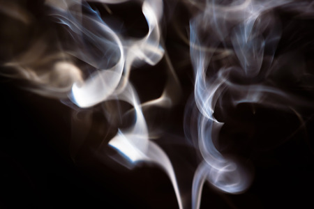 swirl pattern: white smoke from aromatic indian sticks on a black background