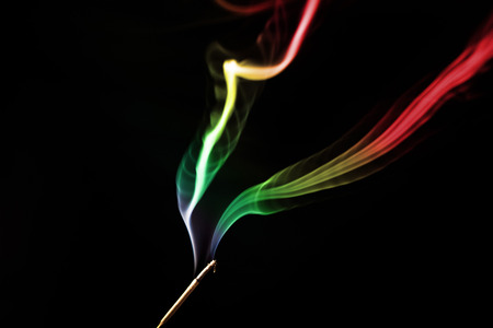 rastafari: colored smoke from aromatic indian sticks on a black background