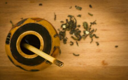 narrow depth of field of herbal tea mate with flowers and stones  on cutting wooden board, focus on bombilla photo