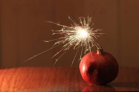 scintillate: red pomegranate with sparkler looking like christmas bomb