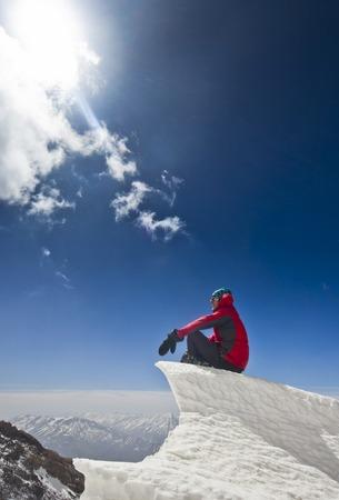 homme heureux en veste rouge avec des mains-up debout sur une falaise dans les montagnes au lever du soleil Banque d'images