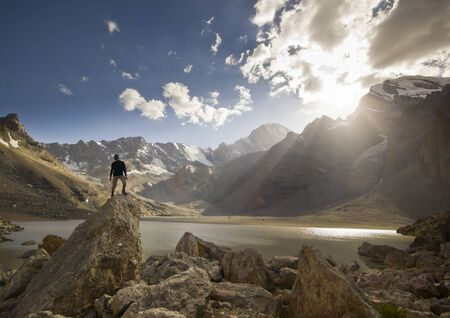 alpinist: man on a cliff at sunset near the mountain lake deep in the mountains Stock Photo