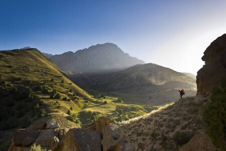 alpinist: man on a cliff at sunset near the mountain green hills and rocks Stock Photo