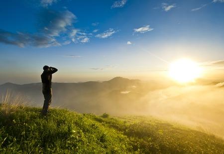 夕日と曇った空で丘の上の写真のカメラを持つ男
