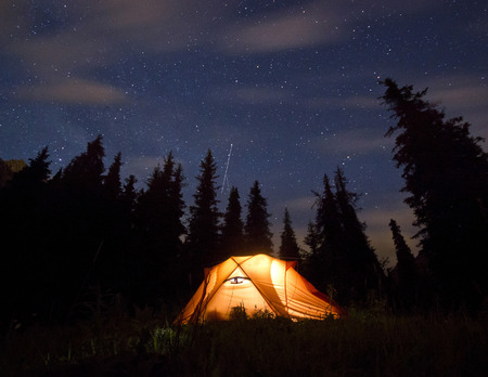 stars above the mountains with tent highlighted by lamp and trees on background