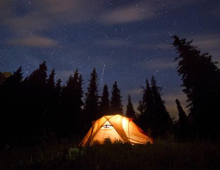 sterren boven de bergen met tent gemarkeerd door lamp en bomen op de achtergrond Stockfoto
