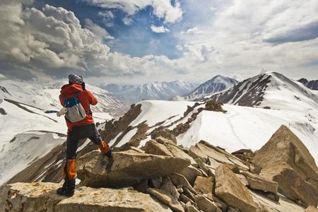 背景に雪の降る山の中の崖の上に立っている人がおすすめ 写真素材