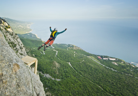 cliff jumping: base-jumper prepears to jump from the cliff at sunrise in the mountains Stock Photo