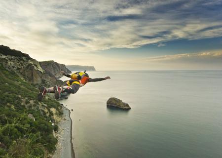 base-jumper prepears te springen van de klif bij zonsopgang in de bergen