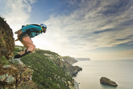 base-jumper prepears to jump from the cliff at sunrise in the mountains Stockfoto