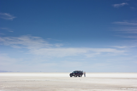 salar de uyuni: car on Salar de Uyuni on white surface and man standing near, Bolivia