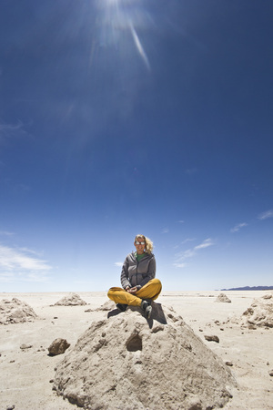 salar de uyuni: blonde girl sitting on a salt heap at Salar de Uyuni in Bolivia with sun shining and clear skyes Stock Photo