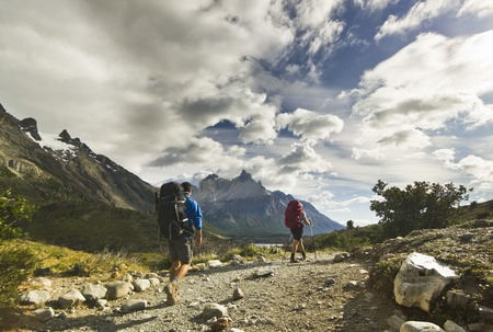 trecking: two men with backpack hiking in patagonia mountains, torres del paine