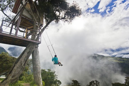 breakage: girl in swing in ecuador mountains near volcan with breakage with cloudy weather