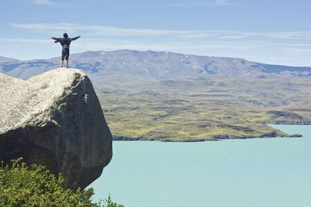 freedom of thought: man on the cliff with hands up in mountains with blue sky and green forest Stock Photo