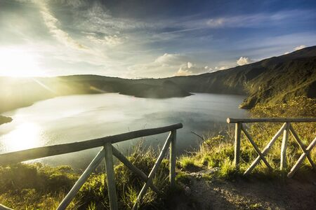 against the sun: fence and crater lake in sunset in ecuador against sun