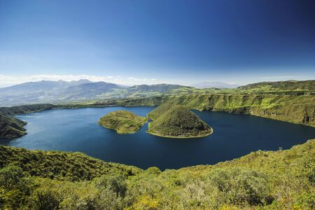 blue volcanic crater lake with two islands at daylight in ecuador