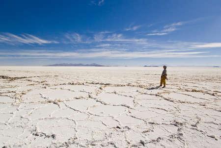 horison: girl standing on salt of salar de uyuni and looking to horison