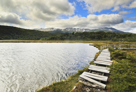 moutains: lake with wooden walkway on shore with moutains on background and sky with clouds Stock Photo