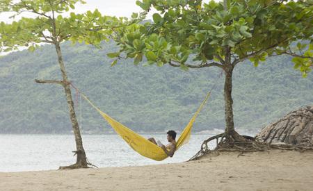 本を読んで熱帯のビーチで 2 本の木の間にハンモックの男