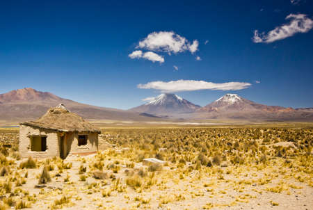 volcanos: small village, several huts, in bolivia near snow covered volcanos near  Sajama in altiplano desert