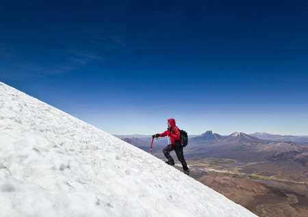 sajama: man in red jacket with ice-axe and backpack climbing on glacier of Sajama Volcano in Bolivia