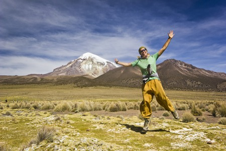 happieness: girl in yellow pants and green t-short jumping and smiling near volcano Sajama in Bolivia with grass field Stock Photo