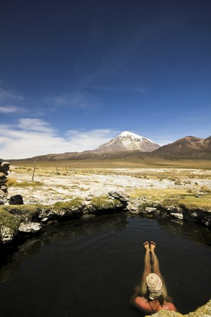 sajama: man resting in hot springs near snow-covered volcano Sajama in Bolivia with bushes of grass