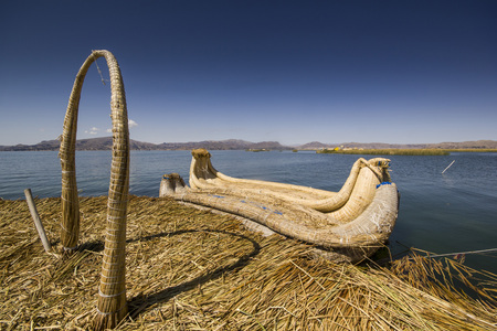 quechua indian: traditional boat of titicaca lake on water, view from floating island uros