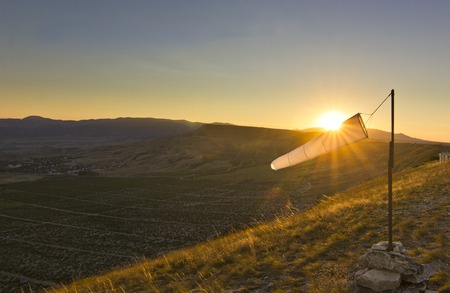 wind blown: paraglider white windsock at sunset in mountains against sun Stock Photo