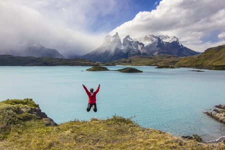 girl in red jacket with hands up jumping above lake in mountains