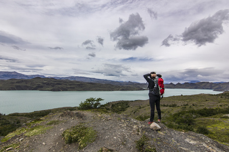 girl with backpack standing on the stone above lake in patagonia Stock Photo