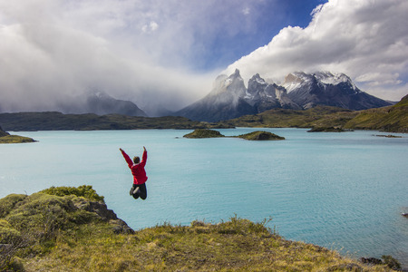 girl in red jacket with hands up jumping above blue lake near torres del payne,patagonia