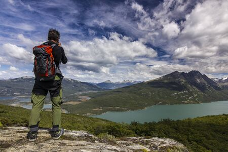 man on the cliff with backpack in mountains with blue clouded sky and green forest in tierra del fuego park