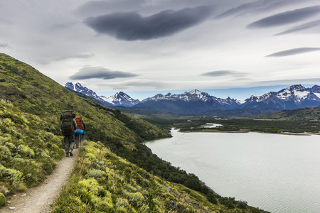 lenticular: two men hiking in patagonia mountains, torres del paine with grey sky Stock Photo