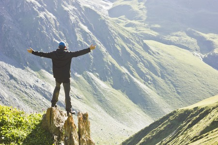 tyan shan mountains: man in black jacket standing on stone with hands-up above mountais at sunset