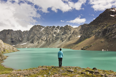 tyan shan mountains: girl in blue jacket standing above blue lake with mountains surrounded
