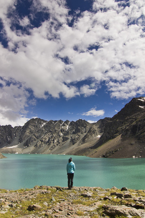 girl in blue jacket standing above blue lake with mountains surrounded