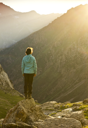 tyan shan mountains: girl in blue jacket standing on stone with hands-up above mountais at sunset