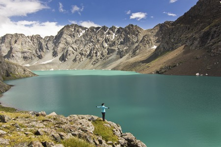 girl in blue jacket standing with hands-up above blue lake in mountains Stock Photo
