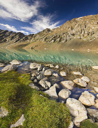 beautiful blue mountain lake with stones on shore and clouds on blue sky Stock Photo