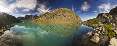 panorama of blue calm mountain lake Alakol with stones on shore and clouds on blue sky in tian-shan mountains at sunrise Stock Photo